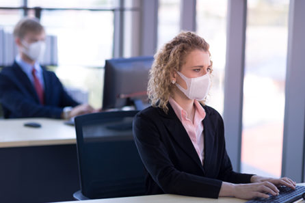 Business woman with curly blonde hair wearing a mask sitting in